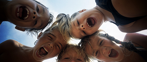 Five children looking down into the camera screaming